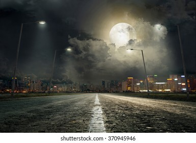 asphalt road leading into the city at night