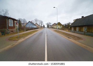 An asphalt road with markings goes into the distance. Along the edges are wooden houses
