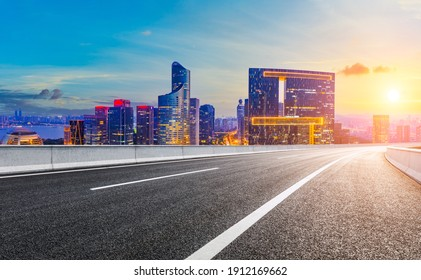Asphalt road and modern city skyline with buildings in Hangzhou at sunset.