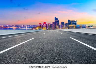 Asphalt road and modern city skyline with buildings in Hangzhou at night.