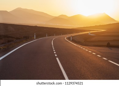 Asphalt road to mountain on sunset.  Picturesque landscape scene. Traveling concept