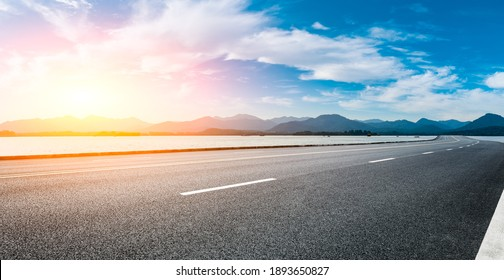 Asphalt road and mountain with sky clouds at sunset.