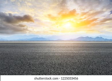 Asphalt road and mountains at beautiful sunset