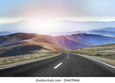 Asphalt road in the mountains with soft sky on the background.