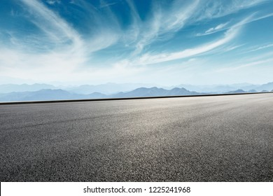 Asphalt road and mountains with white clouds