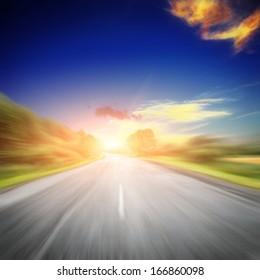 the asphalt road near green fields