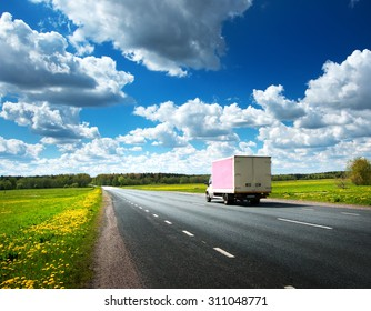 asphalt road on dandelion field with a small truck