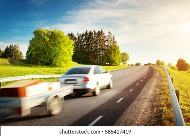 asphalt road on dandelion field with a car with trailer. vehicle moving on sunny evening