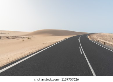 asphalt road on desert sand dune at sunset in Corralejo natural park in Canary islands