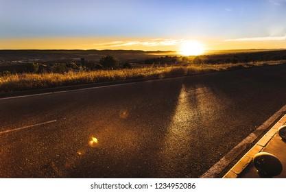 Asphalt road with orange blue sky background and lens flare or sunspot during sunset