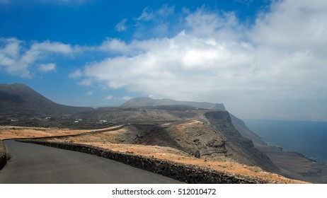 Asphalt road over a cliff above the ocean disappearing over the horizon through volcano mountain hillsides. White clouds on a blue sky. Lanzarote, Canary Islands, Spain