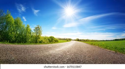 Asphaltstraßenpanorama auf dem Lande an sonniger Frühlingstag