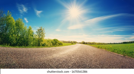 asphalt road panorama in countryside on sunny spring day - Shutterstock ID 1670561386