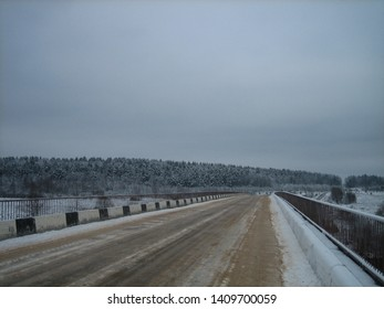 Asphalt road passes over the bridge over the river. On a slippery road dirt, puddles and ice. The bridge has road barriers. The road is strewn with sand. In the distance you can see a dense forest.