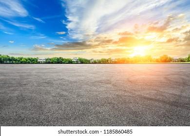 Asphalt road race track and green forest natural landscape at sunset