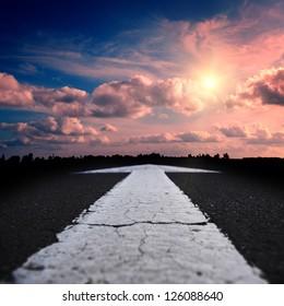 asphalt road at the red sunset