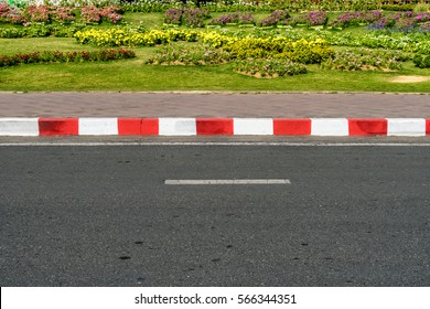 Asphalt road with red and white traffic sign at sidewalk curb