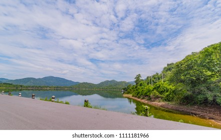 Asphalt road with reservoir on clearly  blue sky and mountains in the background Huaiprue Reservoir, Nakhon Nayok Thailand.