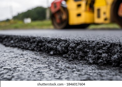 Asphalt road roller with heavy vibration roller compactor press new hot asphalt on the roadway on a road construction site. Heavy Vibration roller at asphalt pavement working. Repairing.
