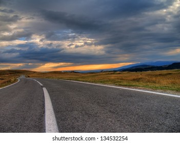 Asphalt road running over the hills close up/Hilly Road/