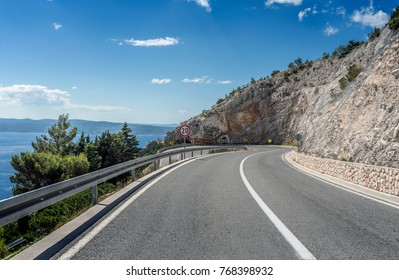 Asphalt road to the sea. Asphalt highway in a sunny day outside the city passing through the cliff next to the sea.