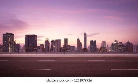 Asphalt road side with beautiful Bangkok city skyline. Night scene