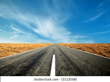 asphalt road straight through the brown field with blue sky and cloud in autumn