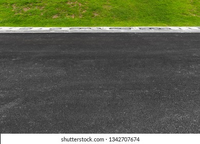 Asphalt road with stripes and green grass texture Background,empty copy space.