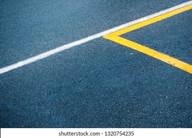 Asphalt road surface with white and yellow lines