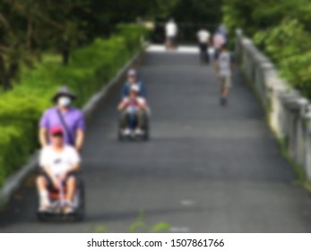 Asphalt road in Taiwan Park. Older people and pedestrians, afternoon leisure and warmth of the sun. There are many people here who are exercising. Intentional blur photography