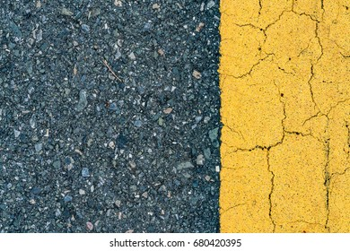 Asphalt road texture with aged yellow line