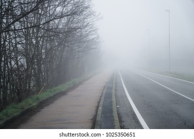 Asphalt road that goes through a misty foggy dark misterious pempty fields.