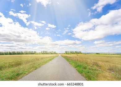Asphalt road through the field with green grass under blue sky with clouds, sunny