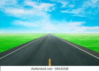 asphalt road through the green field with blue sky