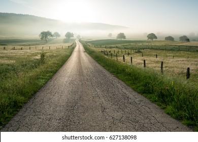 Asphalt Straße durch das grüne Feld und Wolken am blauen Himmel im Sommer.
