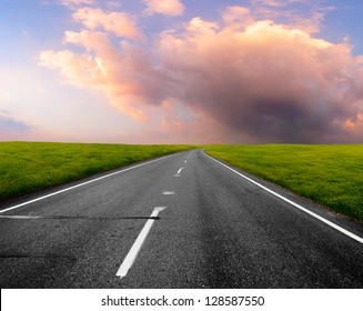 Asphalt road through green meadow with sunset cloudy sky on the background
