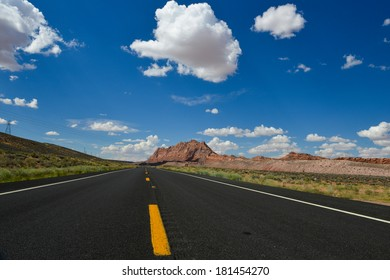 Asphalt road through the vast fields and clouds on blue sky in summer day - Arizona United States
