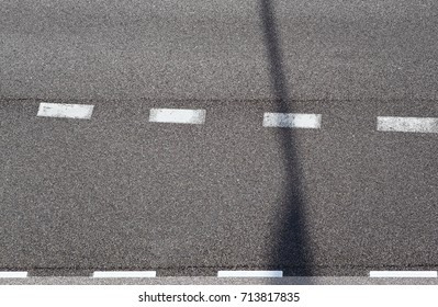 asphalt road top view with horizontal road marking and lantern shadow. Asphalt texture