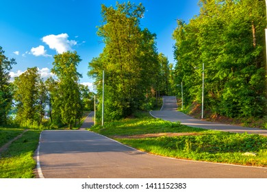 Asphalt road track turn in a sunny green forest among the colorful trees on a summer clear day with a blue sky. Biathlon Stadium, Ufa, Bashkortostan, Russia.