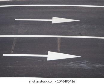 Asphalt road with traffic white arrows