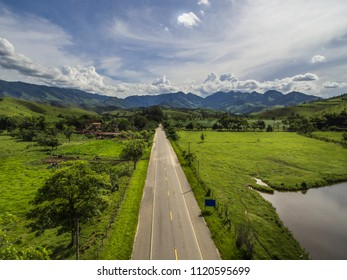 Asphalt road trough the green field with a blue sky with clouds and mountains in the background