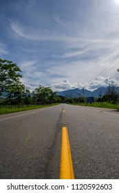 Asphalt road trough the trees with a blue sky with clouds and mountains in the background