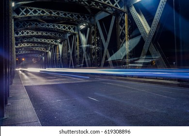 Asphalt road under the steel construction of the illuminated bridge in the city. Night urban scene with car light trails in the tunnel. Citylife, transport and traffic concept. Toned