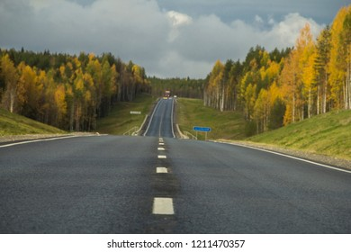 Asphalt road with white markings through the autumn forest. Autumn car trip