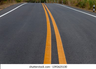 Asphalt road winding on the mountains with yellow and white traffic lines.