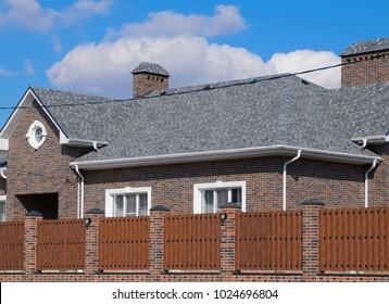 Asphalt shingle. Decorative bitumen shingles on the roof of a brick house. Fence made of corrugated metal
