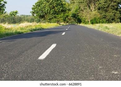 Asphalt surface of a main road going through a rural area