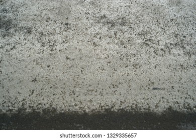Asphalt surface of the road with wet line beneath