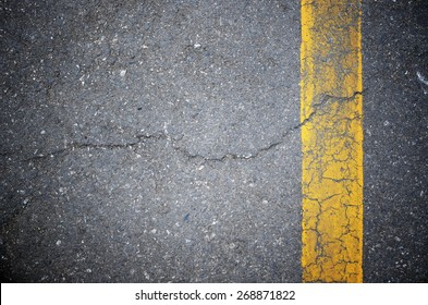 Asphalt texture with a Cracked and Yellow Line