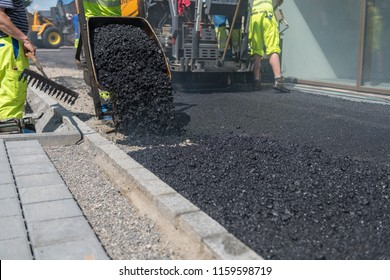 Asphalt is unloaded from a wheelbarrow. The rear part of the asphalt is finished rolled. Asphalt paver in the background.
